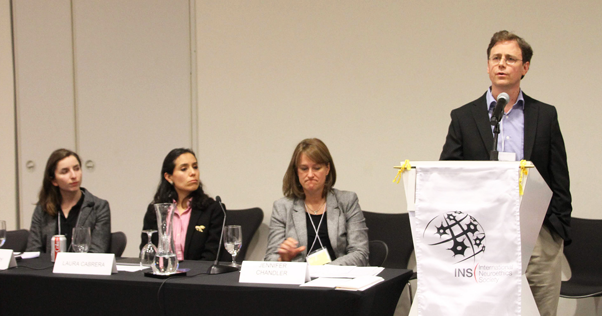 Photo of Lauren Sankary, Laura Cabrera, Jennifer Chandler seated at the table and Eran Klein standing behind the podium