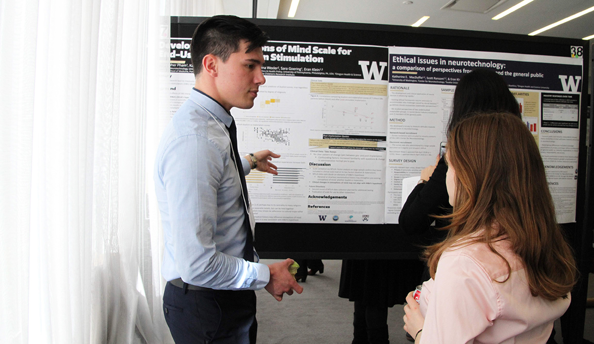Photo of Christopher Pham pointing at his poster while talking to Deena Kopyto
